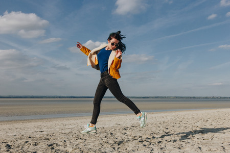 stylish girl in sunglasses jumping on sandy beach, Saint michaels mount, France