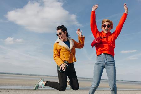 happy girls jumping on sandy beach, Saint michaels mount, Normandy, France