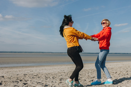 happy friends holding hands and spinning on sandy beach, Saint michaels mount, Normandy, France
