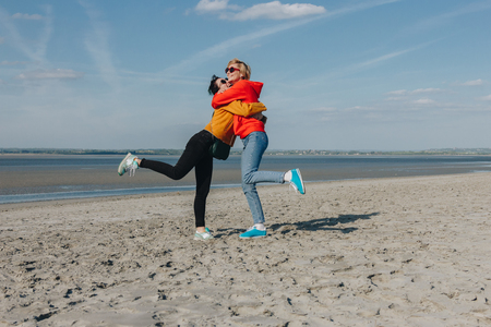 happy friends hugging on sandy beach, Saint michaels mount, Normandy, France