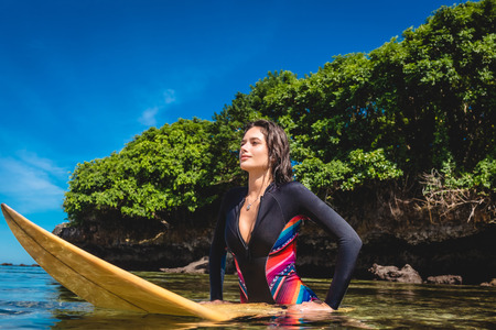 Photo pour young sportswoman in wetsuit on surfing board in ocean at Nusa dua Beach, Bali, Indonesia - image libre de droit