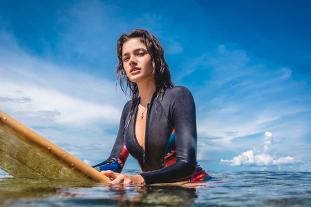 Photo pour portrait of sportswoman in wetsuit on surfing board in ocean at Nusa dua Beach, Bali, Indonesia - image libre de droit