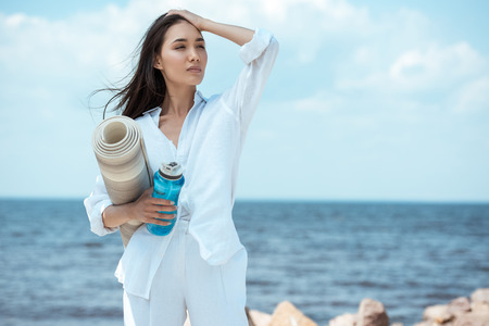 Foto de asian young woman holding sport bottle of water and yoga mat by sea - Imagen libre de derechos