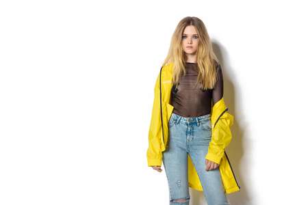 fashionable young woman in transparent shirt and yellow jacket on white