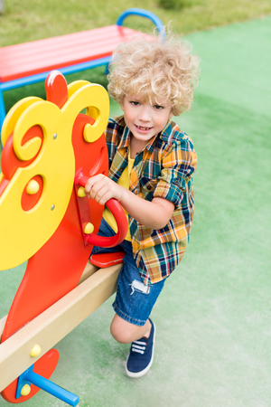 Photo for high angle view of happy curly boy riding on rocking horse at playground - Royalty Free Image