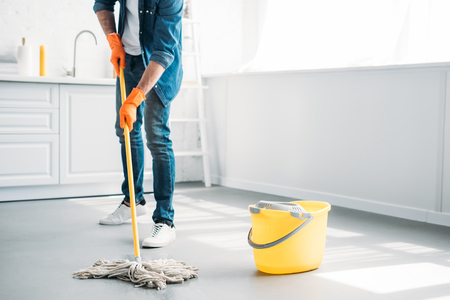 Foto de cropped image of man cleaning floor in kitchen with mop - Imagen libre de derechos