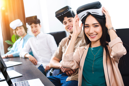 Photo pour multiethnic business partners with virtual reality headsets at table with laptops in modern office - image libre de droit