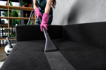 Photo pour partial view of woman in rubber gloves cleaning furniture with vacuum cleaner - image libre de droit