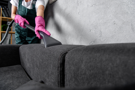 Photo pour cropped shot of woman in rubber gloves cleaning sofa with vacuum cleaner - image libre de droit