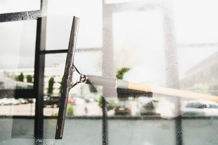Foto de close-up view of cleaning and wiping window with squeegee - Imagen libre de derechos