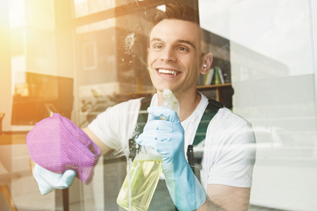 Foto de handsome smiling young man cleaning and wiping window with spray bottle and rag - Imagen libre de derechos