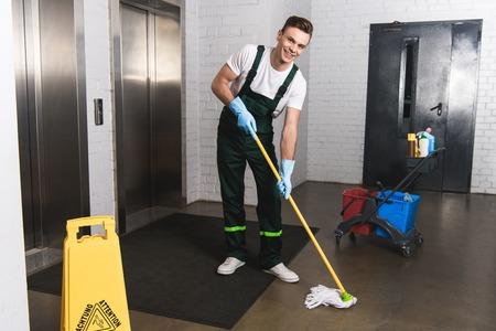 Foto de handsome young janitor mopping floor and smiling at camera - Imagen libre de derechos