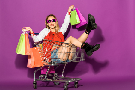 Photo for beautiful young woman in sunglasses holding shopping bags and sitting in shopping trolley on violet - Royalty Free Image