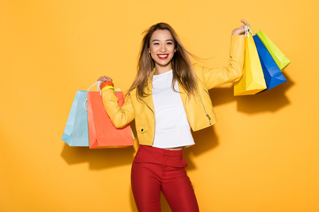 Foto de smiling stylish asian woman with shopping bags on yellow background - Imagen libre de derechos