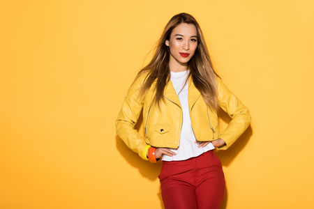 young attractive female model posing on yellow background