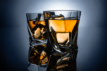 Photo for two glasses of whiskey with ice cubes, on dark grey background - Royalty Free Image