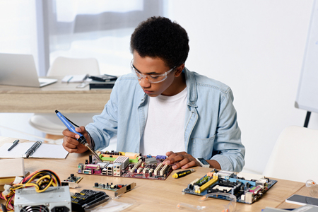 Photo for african american teenager soldering computer circuit with soldering iron at home - Royalty Free Image