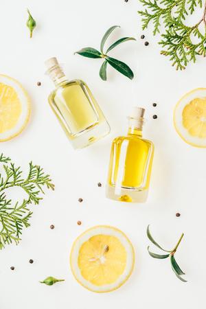 Foto de top view of bottles of fresh perfume with green branches and lemon slices on white - Imagen libre de derechos