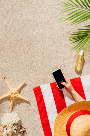 cropped shot of woman in hat using smartphone while relaxing on sandy beach
