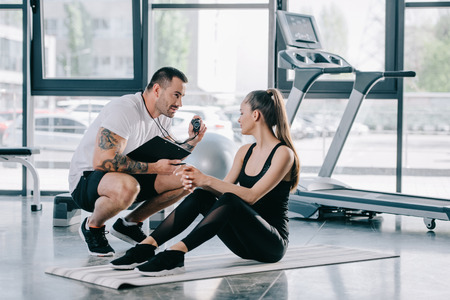 Photo pour male personal trainer showing timer to young athletic woman on fitness mat at gym - image libre de droit