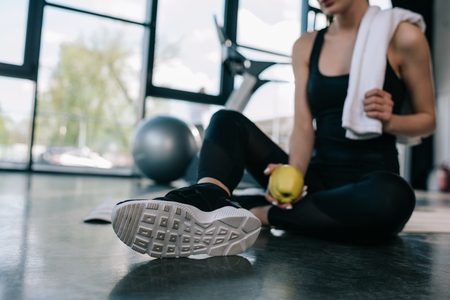 Foto de cropped shot of sportswoman resting with towel and apple on gym floor - Imagen libre de derechos