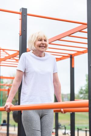 Foto de happy senior sportswoman exercising on sports ground - Imagen libre de derechos