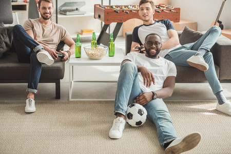 young black man sitting on rug with ball between two friends playing video game with joysticks in hands