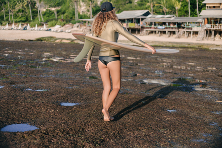 Photo pour rear view of young woman in wetsuit walking by beach with surfboard in evening - image libre de droit