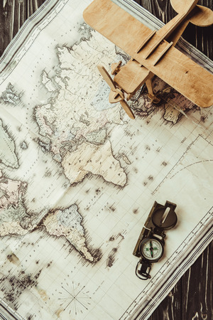 top view of map, wooden toy plane and compass on dark wooden surface