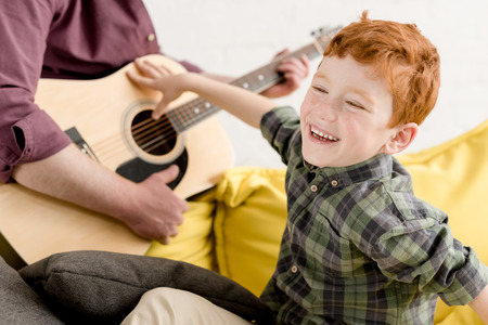 cropped shot of cute little boy laughing and father playing guitarの写真素材