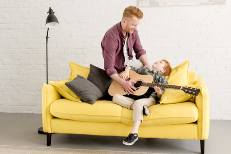 happy redhead father and son playing acoustic guitar together at homeの写真素材