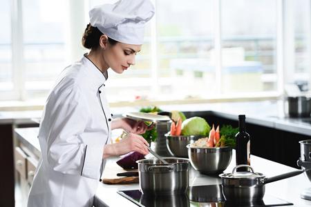 Photo pour Woman chef cooking in pan on kitchen stove - image libre de droit