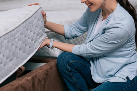 Photo pour cropped shot of smiling woman choosing orthopedic mattress in furniture store - image libre de droit