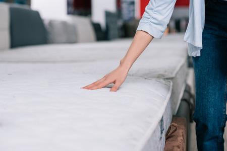 Photo pour partial view of woman touching orthopedic mattress in furniture shop - image libre de droit