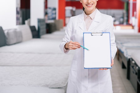 cropped shot of smiling shop assistant in white coat pointing at empty notepad in hand in furniture shop with arranged mattresses
