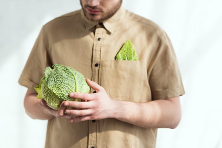 partial view of man with fresh savoy cabbage in hands, vegan lifestyle concept