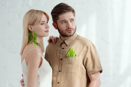 woman with earring made of arugula and boyfriend with savoy cabbage leaf in pocket, vegan lifestyle concept