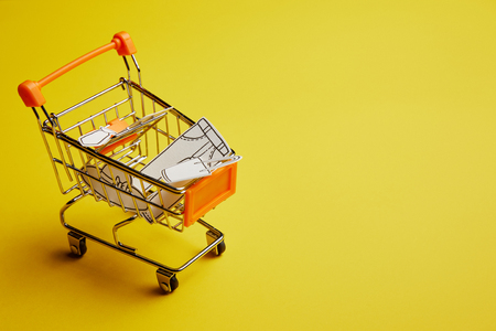Photo pour close up view of little shopping cart with clothes made of paper on yellow background - image libre de droit