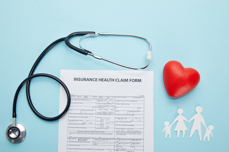 top view of insurance health claim form, paper cut family, red heart symbol and stethoscope on blue