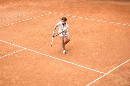 retro styled male tennis player with racket playing game on tennis court