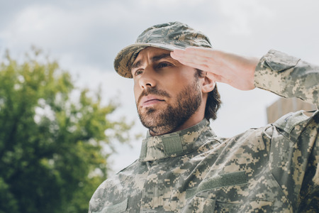 Foto per portrait of confident soldier in military uniform with cloudy sky on background - Immagine Royalty Free