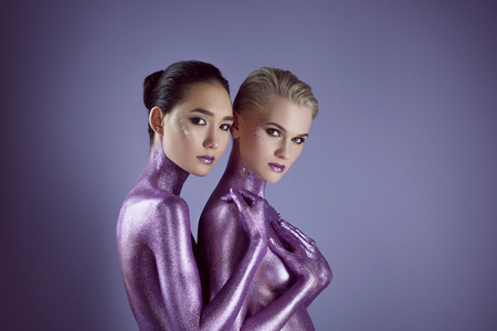 multicultural naked women in purple glitter hugging each other, isolated on violet