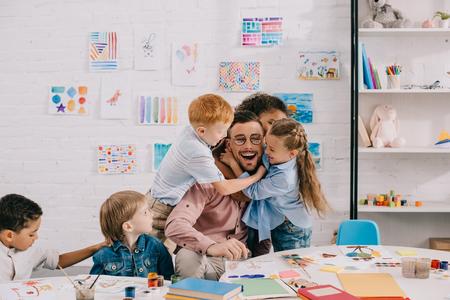 Photo pour interracial kids hugging happy teacher at table in classroom - image libre de droit