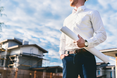 Photo pour cropped shot of architect in white shirt with blueprint standing at yard in front of building house - image libre de droit