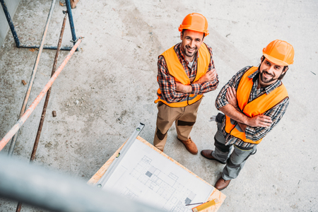 Photo pour high angle view of smiling builders with blueprint standing at construction site and looking at camera - image libre de droit