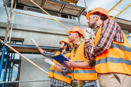 Photo pour group of builders in hard hats and reflective vests pointing at building house - image libre de droit