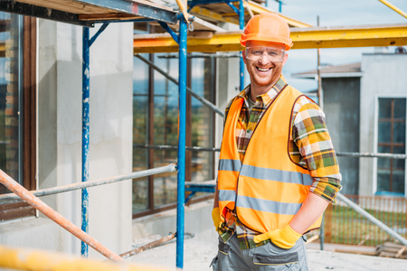 Photo pour handsome smiling builder in reflective vest and hard hat looking at camera at construction site - image libre de droit