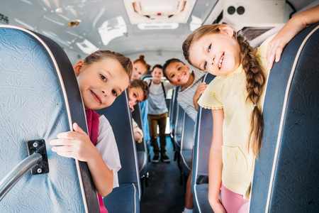Photo pour group of cute schoolchildren riding on school bus and looking at camera - image libre de droit