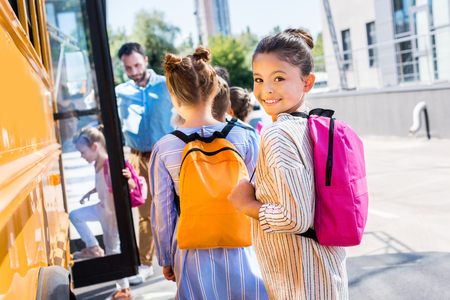 Foto de little schoolgirl entering school bus with classmates while teacher standing near door - Imagen libre de derechos