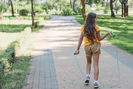 Foto de rear view of cute kid holding jumping rope and walking in park - Imagen libre de derechos